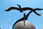 A zoom in on the pelican sculpture that is situated in the middle of the roundabout. A group of real pelicans flies by in the distance.